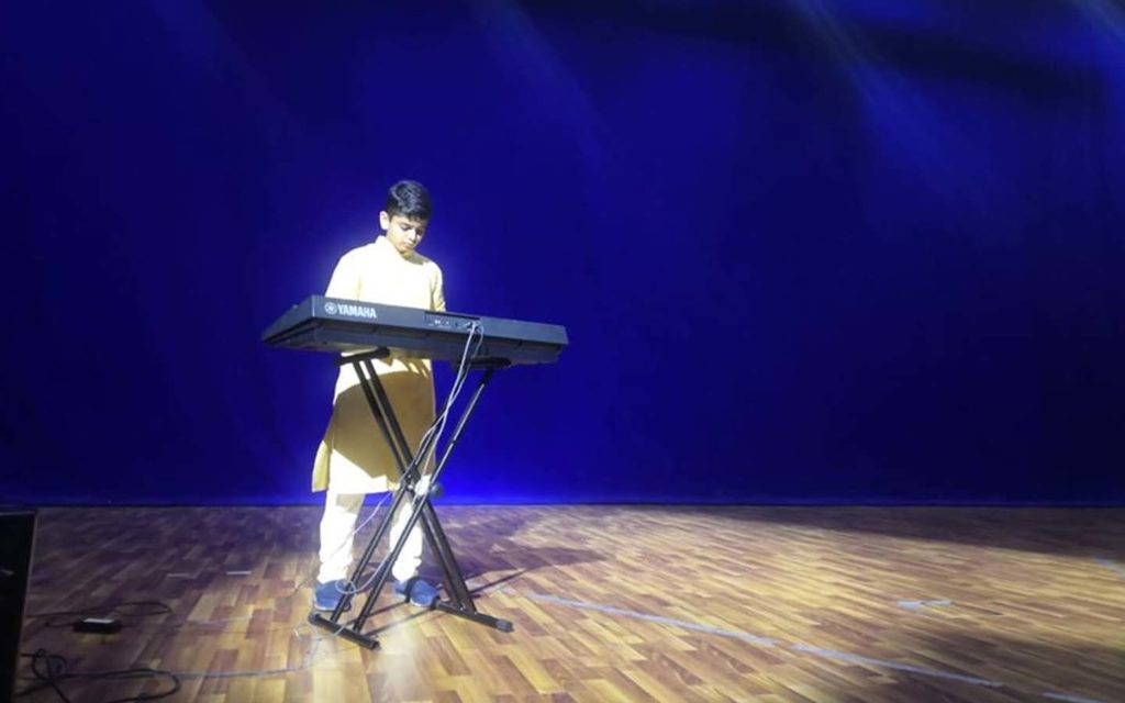 JSS International School student playing piano as an extra-curricular activity