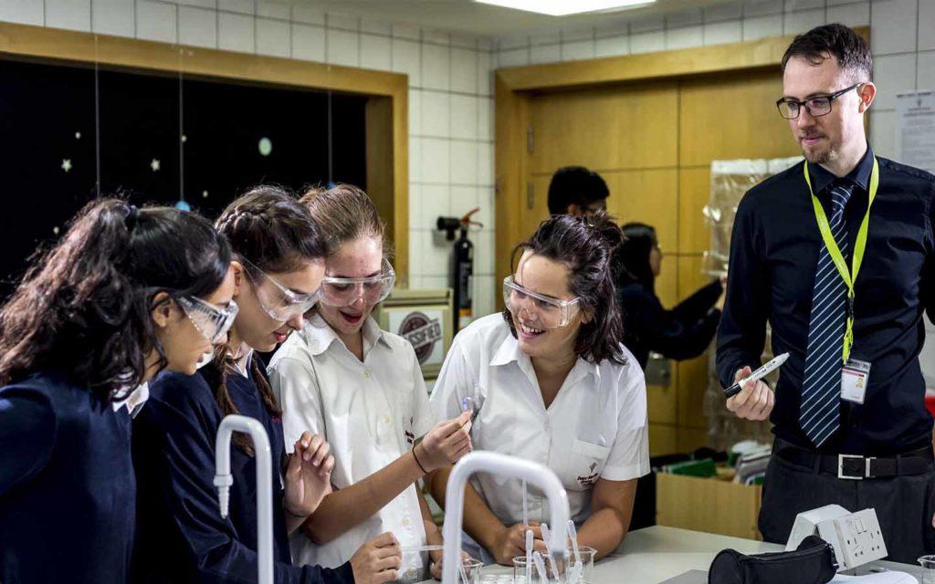 معلم مع طالبات في المختبر